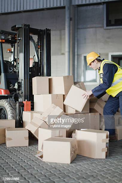 Worker loading boxes onto forklift