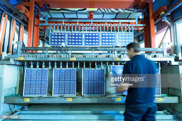 Worker loading circuit boards into processing machine in circuit board factory