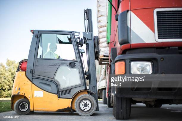 Worker loading pallet with a forklift into a truck.