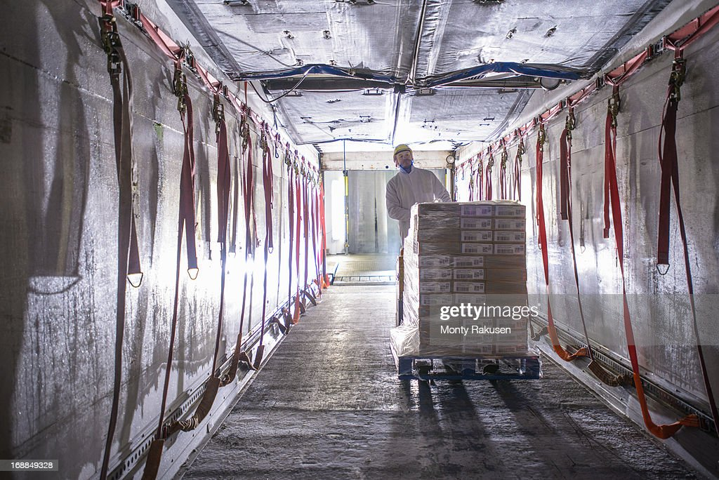 Worker loading products into freezer truck of food factory