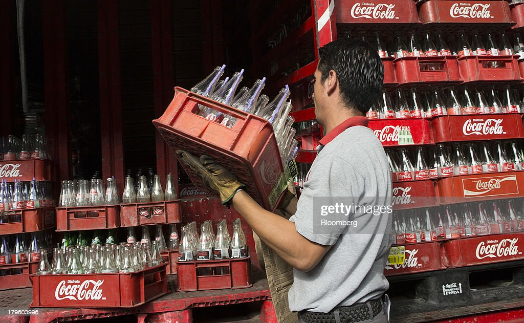 A worker loads a delivery truck with empty Coca-Cola bottles in Mexico City, Mexico, on Thursday, Sept. 5, 2013. Coca-Cola Femsa SAB, a bottler and distributor of Coca-Cola products in Mexico, agreed to buy Brazils Spaipa SA Industria Brasileira de Bebidas in a cash deal with a total transaction value of $1.86 billion. Photographer: Susana Gonzalez/Bloomberg via Getty Images