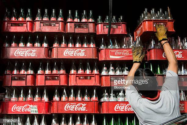 A worker loads a delivery truck with empty CocaCola bottles in Mexico City Mexico on Thursday Sept 5 2013 CocaCola Femsa SAB a bottler and...