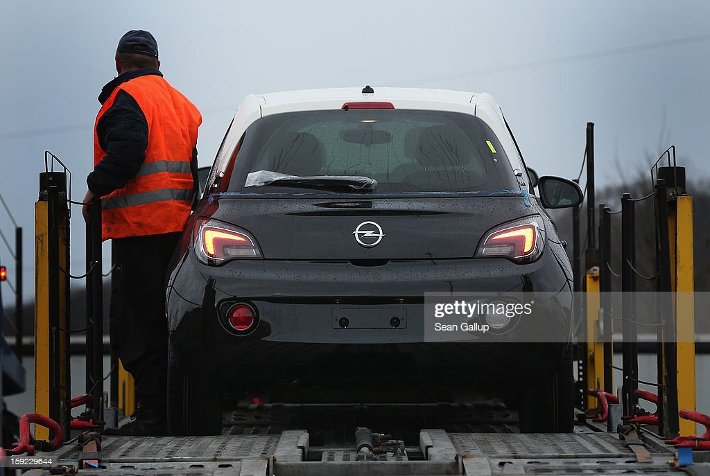 A worker loads a finished Opel Adam car onto a truck at a factory parking lot shortly after a celebration to mark the launch of the new Opel compact car at the Opel factory on January 10, 2013 in Eisenach, Germany. Opel employees hope the car will help the compny return to profits after years of sagging sales and the announcement of the Bochum factory closure in 2016.
