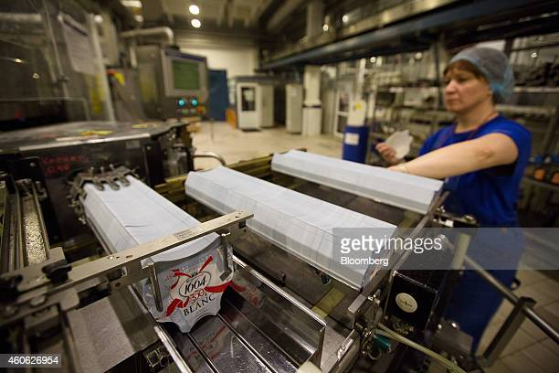 A worker loads a machine with labels destined for bottles of Kronenbourg 1664 Blanc beer on the production line at the OAO Baltika brewery operated...
