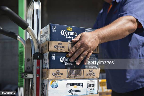 A worker loads cases of Constellation Brands Inc Corona beer on a cart during a delivery in Ottawa Illinois US on Tuesday June 27 2017 Constellation...