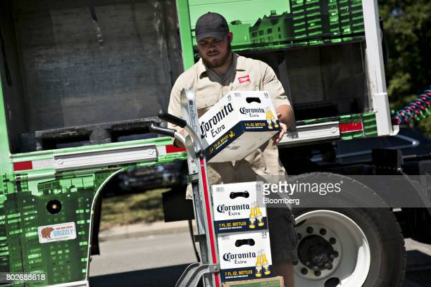 A worker loads cases of Constellation Brands Inc Corona beer onto a cart during a delivery in Ottawa Illinois US on Tuesday June 27 2017...