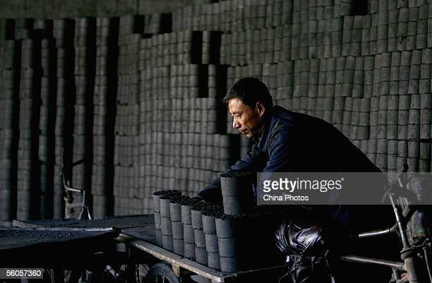 A worker loads coal briquettes on a tricycle in a coal briquette factory on October 31 2005 in Beijing China Coal supplies 70 percent of the energy...