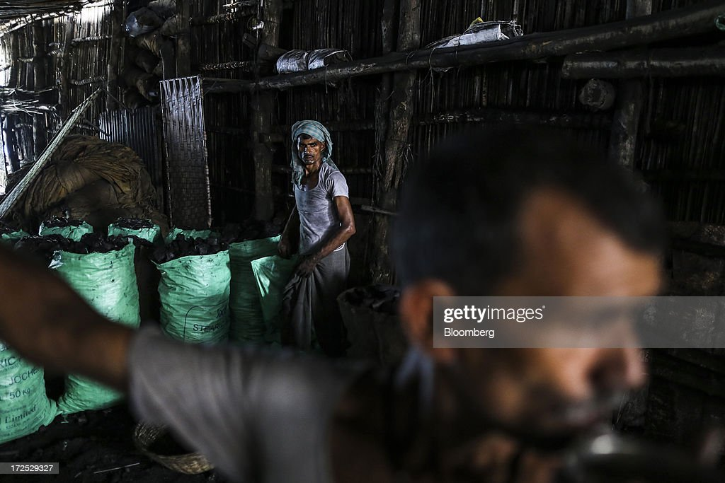 A worker loads coal into a bag at a coal wholesale market in Mumbai, India, on Tuesday, July 2, 2013. India, the worlds third-largest coal consumer, imported 43 percent more of the fuel than a year ago on increased demand from power stations and steelmakers, according to shipping data, and is set to eclipse China as the top importer of power station coal by 2014. Photographer: Dhiraj Singh/Bloomberg via Getty Images