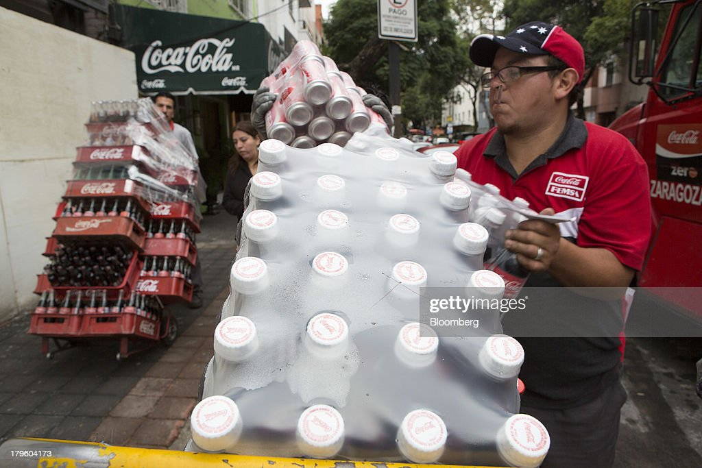A worker loads Coca-Cola bottles onto a hand truck while making deliveries in Mexico City, Mexico, on Thursday, Sept. 5, 2013. Coca-Cola Femsa SAB, a bottler and distributor of Coca-Cola products in Mexico, agreed to buy Brazils Spaipa SA Industria Brasileira de Bebidas in a cash deal with a total transaction value of $1.86 billion. Photographer: Susana Gonzalez/Bloomberg via Getty Images