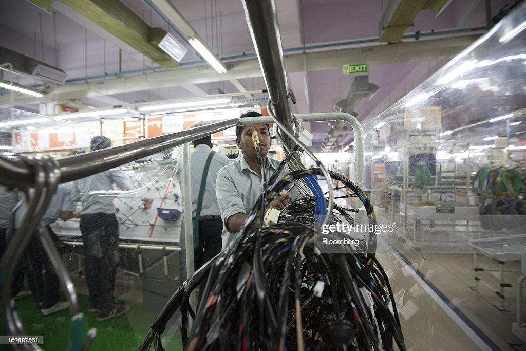 A worker loads finished wire harnesses onto a trolley at the Motherson Sumi Systems Ltd. wiring harness plant in Faridabad, India, on Thursday, Feb. 28, 2013. Motherson Sumi Systems Ltd., 25 percent owned by Sumitomo Electric Industries Ltd. and India's biggest auto parts maker, supplies rear view mirrors, bumpers and body panels to clients including Porsche Automobil Holding SE, Bayerische Motoren Werke AG and Volkswagen AG. Photographer: Brent Lewin/Bloomberg via Getty Images