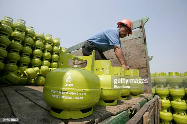 A worker loads gas canisters into a truck at a PT Pertamina depot in Jakarta Indonesia on Thursday Oct 4 2007 The government is distributing free of...