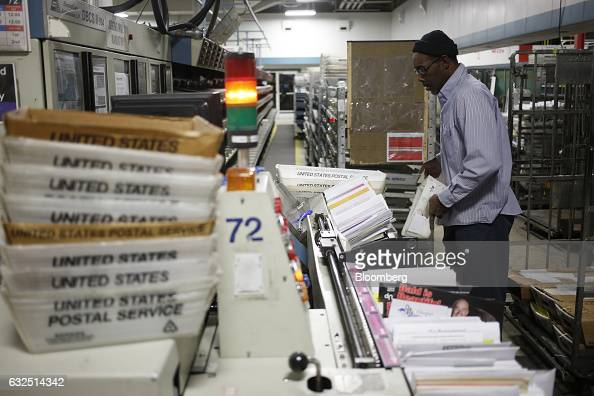 A worker loads mail onto an automated sorting machine at the United States Postal Service sorting center in Louisville Kentucky US on Friday Jan 13...