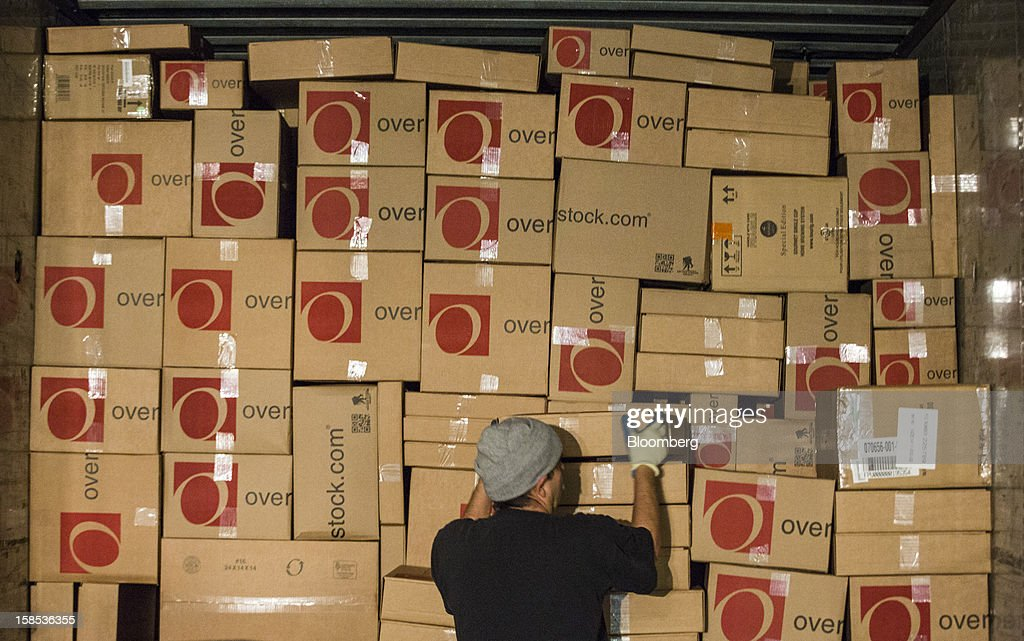 A worker loads orders on to a United Parcel Service Inc. (UPS) truck at the Overstock.com Inc. distribution center in Salt Lake City, Utah, U.S., on Tuesday, Dec. 18, 2012. Online sales may grow to a record $43.4 billion in the last two months of the year, a 17 percent increase from last year, according to ComScore Inc. Photographer: Ken James/Bloomberg via Getty Images