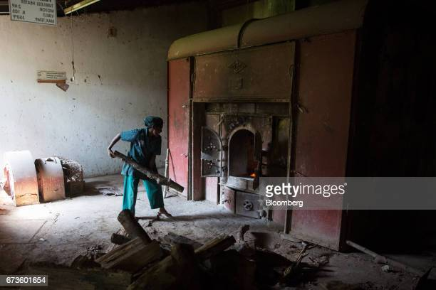 A worker loads rubberwood into a furnace at the factory of the Geragama Tea Estate operated by Pussellawa Plantations Ltd in Pilimathalawa Central...