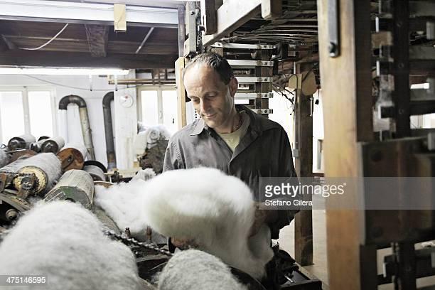 Worker looking at fleece in wool factory