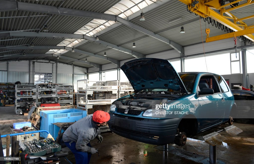 A worker looks at a damaged car at a car recovery and recycling company near Munich, southern Germany, on February 6, 2013. AFP PHOTO/CHRISTOF STACHE