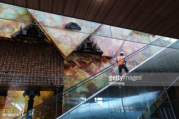 A worker looks at a mural as he rides on an escalator inside the newly built Terminal 2 of the Chhatrapati Shivaji International Airport operated by...