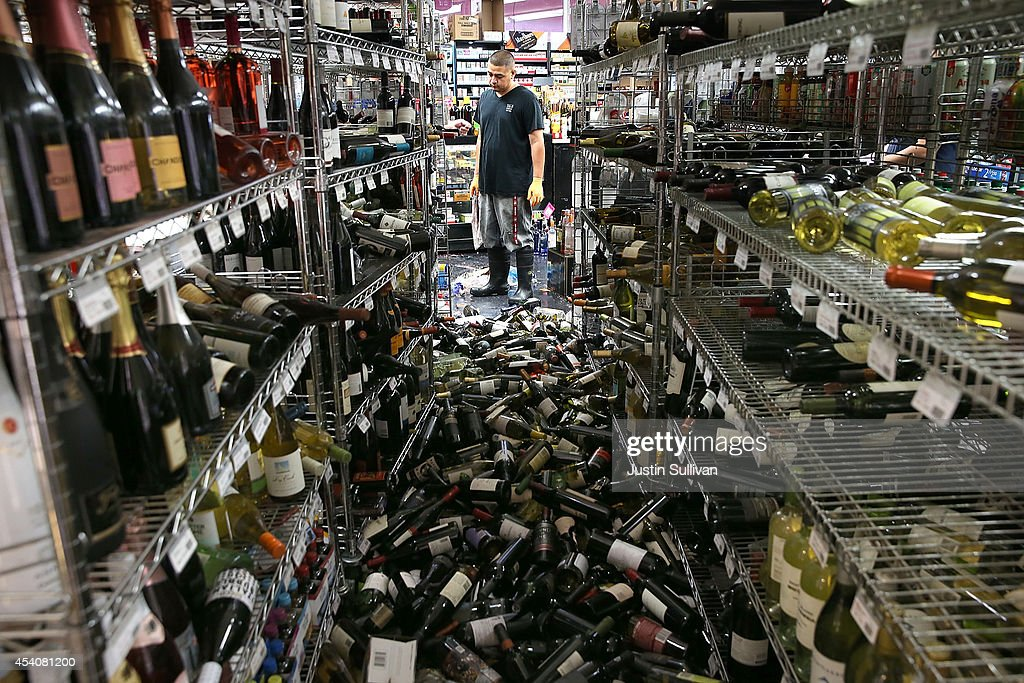 A worker looks at a pile of wine bottles that were thrown from the shelves at Van's Liquors following a reported 60 earthquake on August 24 2014 in...