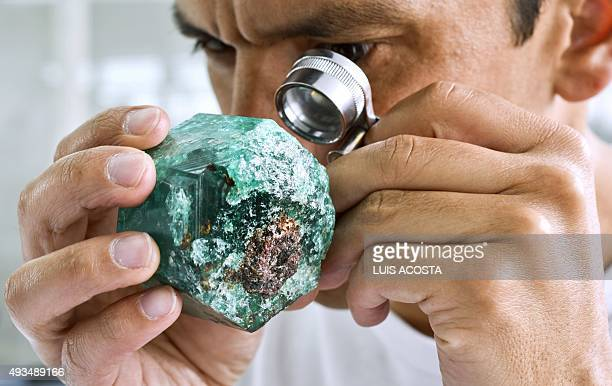 A worker looks at an emerald at the workshop of Muzo Emerald Company in Bogota on October 16 2015 Colombian emeralds are considered to be the most...