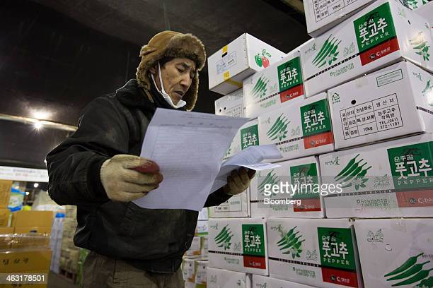A worker looks at papers as he inspects boxes of green chilli peppers at Garak Market operated by Seoul AgroFisheries Food Corp in Seoul South Korea...