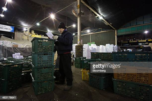 A worker looks at papers as he inspects shitake mushrooms at Garak Market operated by Seoul AgroFisheries Food Corp in Seoul South Korea on Wednesday...