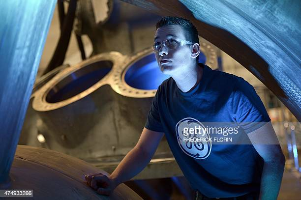 A worker looks at the 9HA Gas Turbine at the US conglomerate General Electric plant in Belfort eastern France on May 28 2015 AFP PHOTO/FREDERICK...