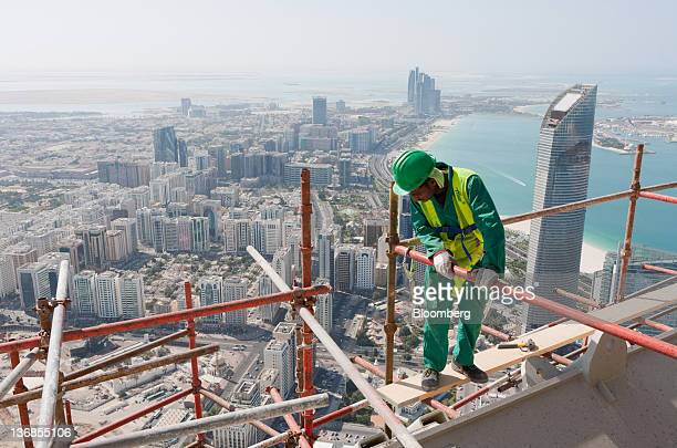 A worker looks down from a scaffolding platform on a residential tower construction above the Central Market an Aldar PJSC project in Abu Dhabi...