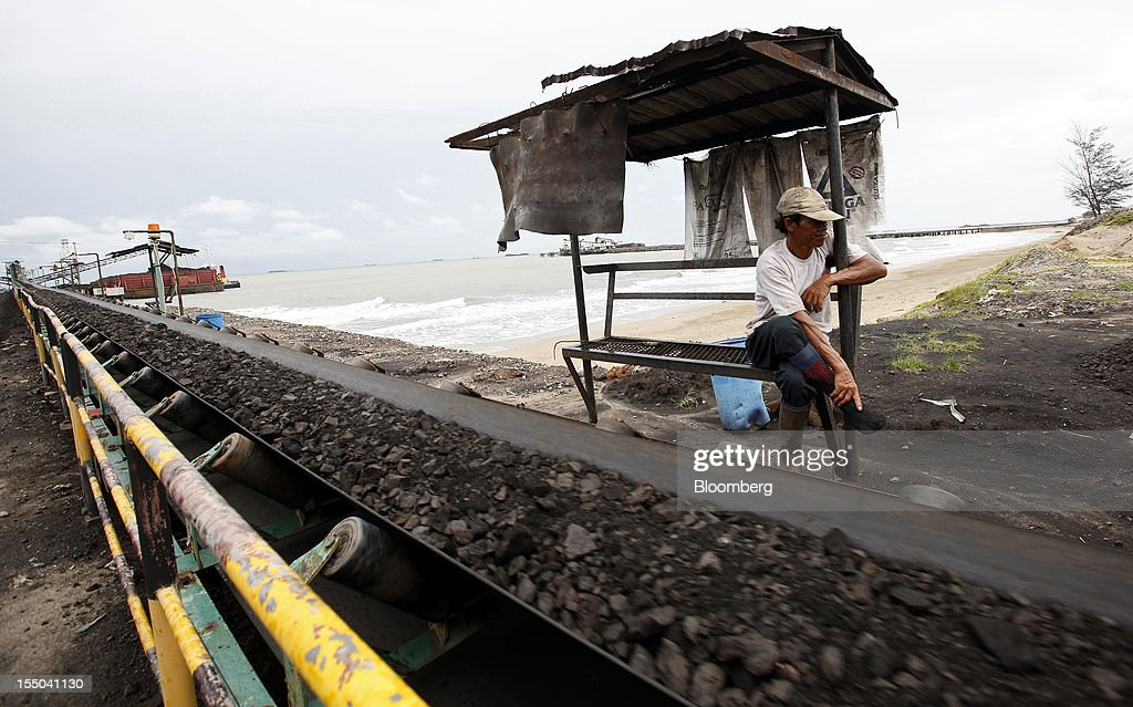 A worker looks on as a conveyor transports coal to the loading dock of the PT Exploitasi Energi Indonesia operations in Asam-Asam, South Kalimantan, Indonesia, on Monday Oct. 29, 2012. Indonesia, the world's largest exporter of coal for electricity generation, will reduce the amount of the fuel that producers must sell to buyers inside the country for next year by 9.4 percent. Photographer: Dadang Tri/Bloomberg via Getty Images