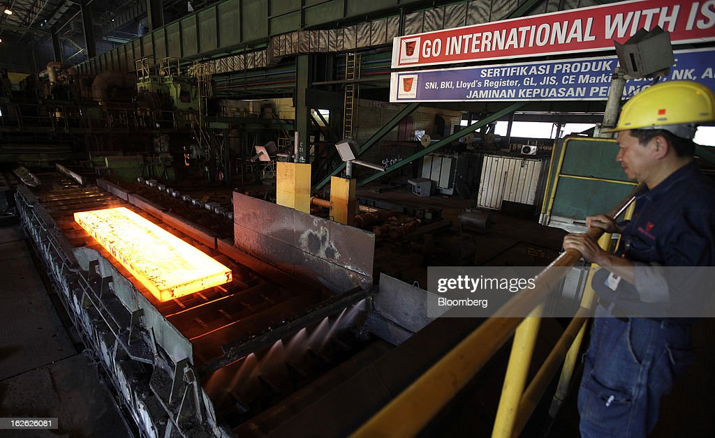 A worker looks on as a steel slab moves along the production line in the hot strip mill area of the PT Krakatau Steel plant in Cilegon, Banten province, Indonesia, on Thursday, Feb. 21, 2013. Krakatau Steel is Indonesia's biggest maker of the metal. Photographer: Dadang Tri/Bloomberg via Getty Images