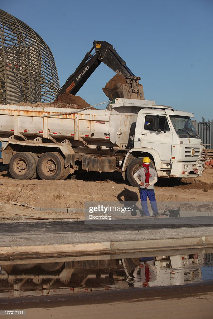 A worker looks on as a truck is filled with soil at the Metropolitano Barra Shopping center under construction in Rio de Janeiro, Brazil, on Wednesday, Aug. 21, 2013. Latin America's largest economy created 7,154 manufacturing jobs and 4,899 construction jobs in July, down from 24,718 and 25,433 new posts a year ago. Photographer: Dado Galdieri/Bloomberg via Getty Images