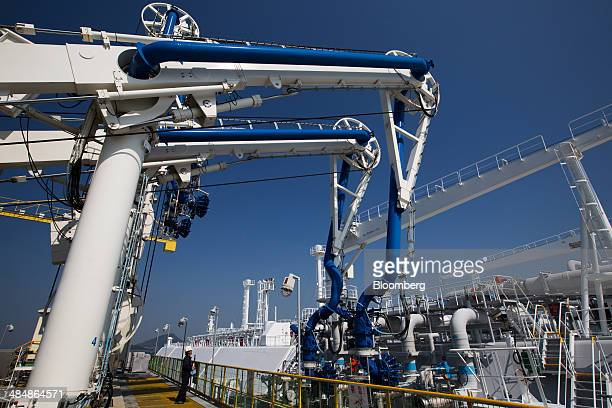 A worker looks on as the Tangguh Palung liquefied natural gas tanker right operated by Tangguh LNG is connected to pipelines while it sits moored at...