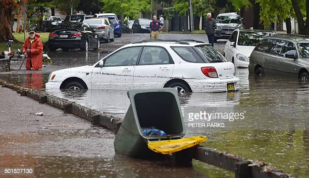 A worker looks on past inundated cars on a flooded street after a storm in the eastern suburbs of Sydney on December 16 2015 Sydney was smashed by a...