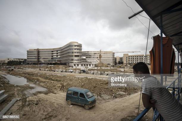 A worker looks out at the site of the under construction Evergrande International Hospital inside the Hainan Boao Lecheng...