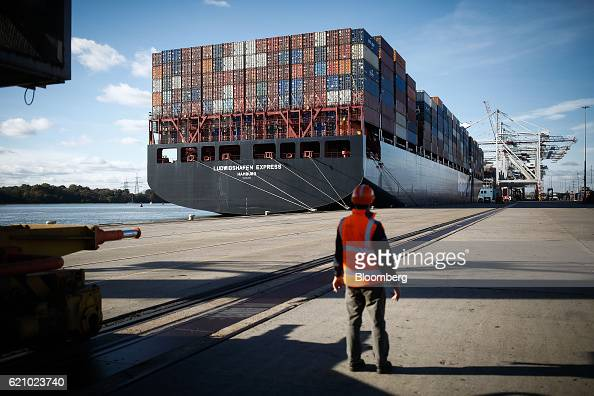 A worker looks out onto the Ludwigshafen Express container vessel operated by HapagLloyd AG as it arrives on the dockside at the container terminal...
