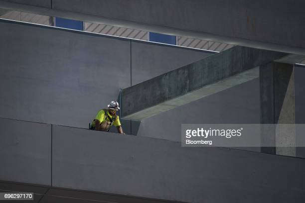 A worker looks over the edge of a building under construction in Sacramento California US on Tuesday June 6 2017 As the cost of daily life tests the...
