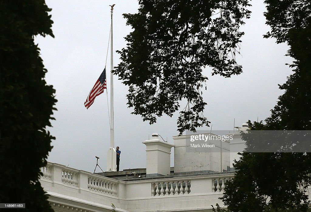 A worker lowers the American flag on the White House to half staff on July 20 2012 in Washington DC US President barack Obama orded flags be be flown...