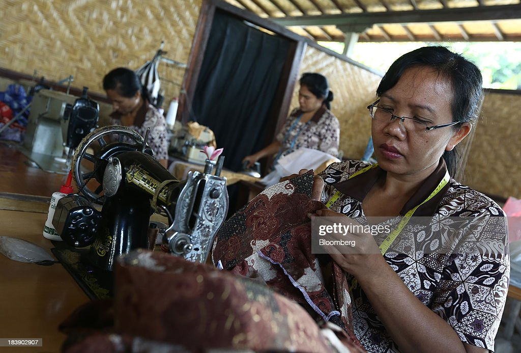 A worker makes a batik shirt at a store in Gianyar, Bali, Indonesia, on Tuesday, Oct. 8, 2013. Bank Indonesia said it will regulate currency hedging by individuals and companies, including state-owned firms, to help stabilize Asias most-volatile currency. Photographer: SeongJoon Cho/Bloomberg via Getty Images