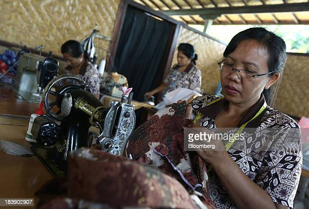 A worker makes a batik shirt at a store in Gianyar Bali Indonesia on Tuesday Oct 8 2013 Bank Indonesia said it will regulate currency hedging by...