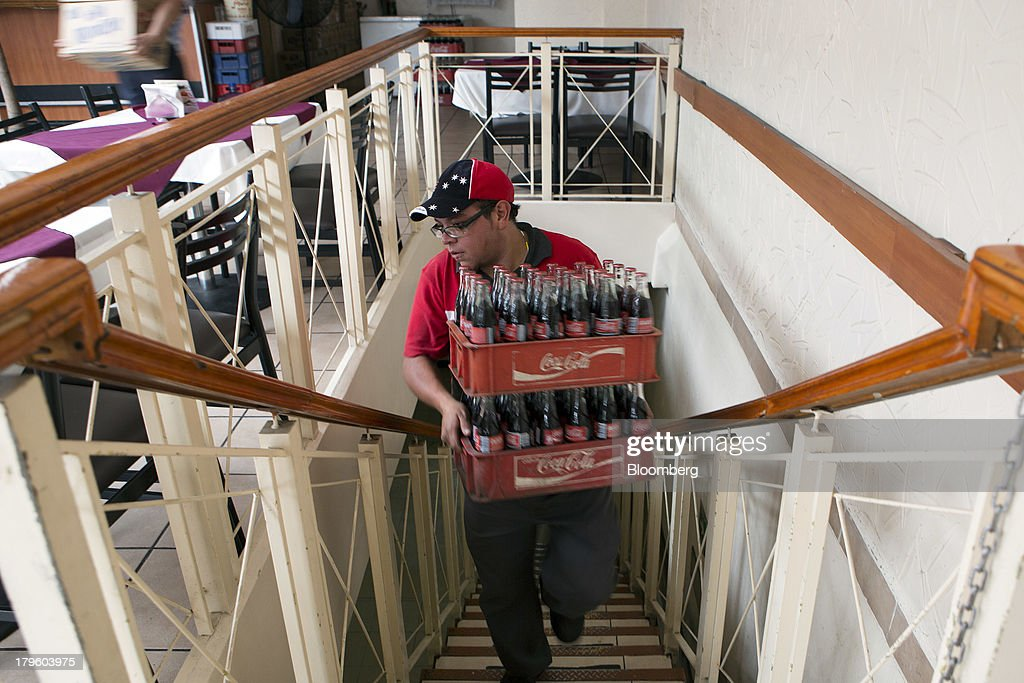 A worker makes a delivery of Coca-Cola bottles to a restaurant in Mexico City, Mexico, on Thursday, Sept. 5, 2013. Coca-Cola Femsa SAB, a bottler and distributor of Coca-Cola products in Mexico, agreed to buy Brazils Spaipa SA Industria Brasileira de Bebidas in a cash deal with a total transaction value of $1.86 billion. Photographer: Susana Gonzalez/Bloomberg via Getty Images