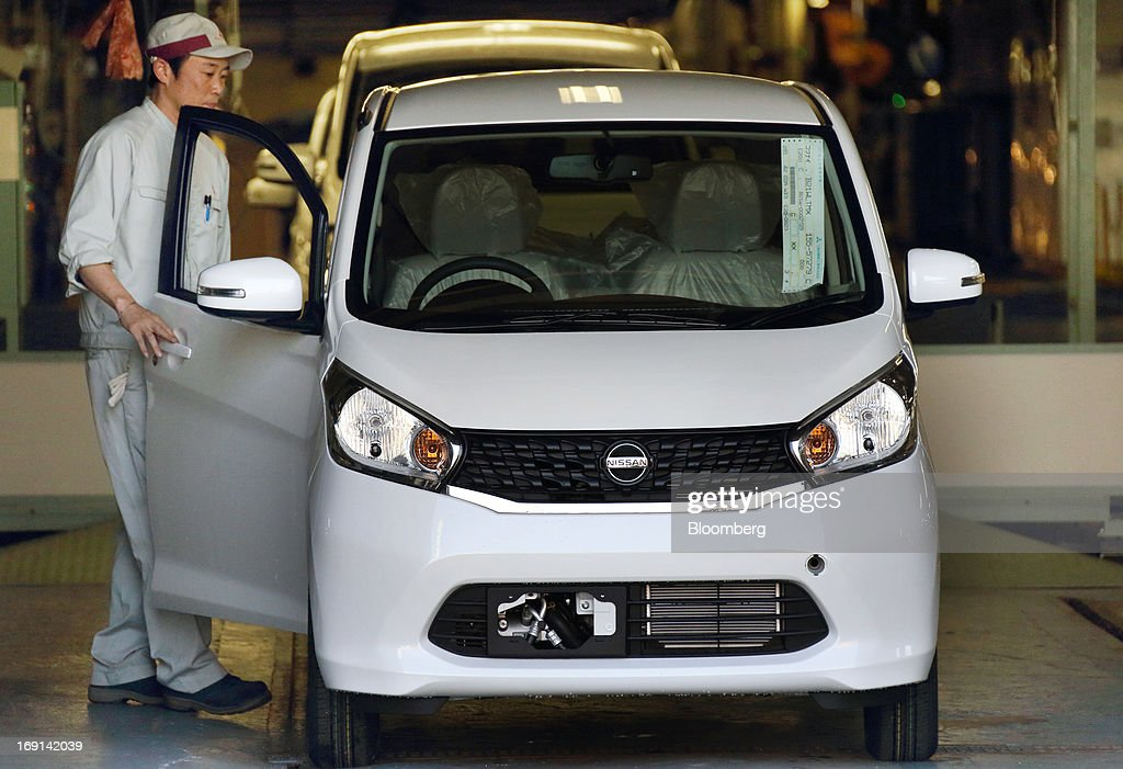 A worker makes a final inspection of a Nissan Motor Co. DAYZ minicar on the production line of the Mitsubishi Motors Corp. Mizushima plant in Kurashiki City, Okayama Prefecture, Japan, on Monday, May 20, 2013. Nissan will start selling the first minicar it jointly developed with Mitsubishi Motors in Japan next month amid increasing demand from the nation's consumers for smaller and cheaper vehicles. Photographer: Tomohiro Ohsumi/Bloomberg via Getty Images