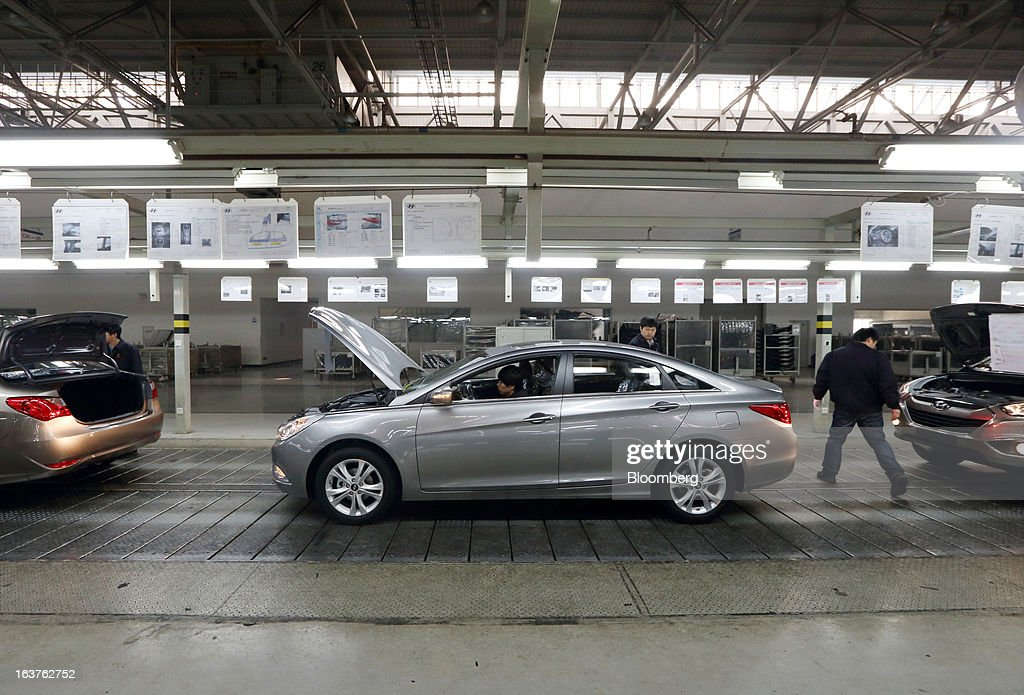 A worker makes a final inspection on a Beijing Hyundai Motor Co. car on the production line at the company's plant in Beijing, China, on Friday, March 15, 2013. The joint venture between Beijing Automotive Industry Holding Co. and Hyundai Motor Co., has three plants in the city, manufacturing 11 kind of models. Photographer: Tomohiro Ohsumi/Bloomberg via Getty Images