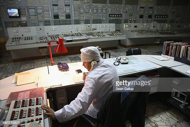 A worker makes a phone call in the control room of reactor number two inside the former Chernobyl nuclear power plant on September 29 2015 near...