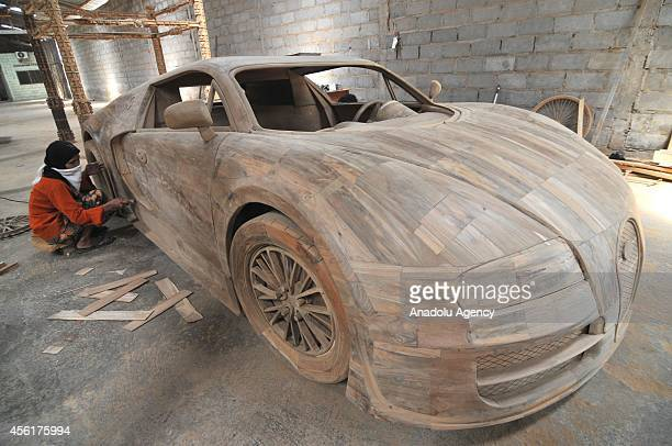 A worker makes a realsize replica of Bugatti Veyron Super Sport car from wood in Boyolali Central Java Indonesia on September 26 2014 A replica of...