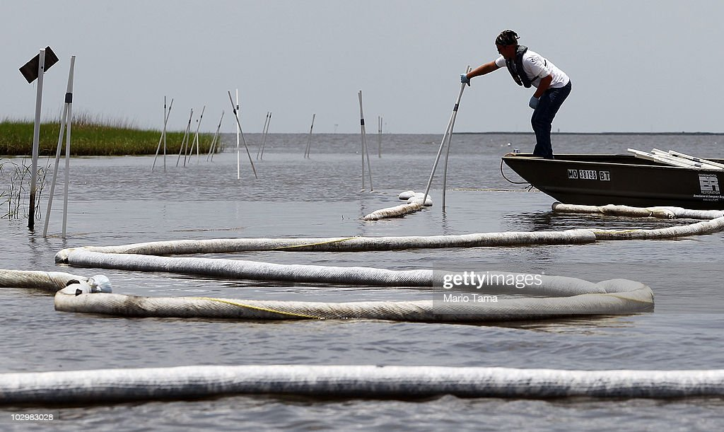 A worker makes adjustments to oil boom July 19, 2010 near Pointe Aux Chenes, Louisiana. The tribe has lived along the threatened marshes for more than one hundred years and make their livelihood on the water. Officials are concerned about leakage reportedly spotted near BP's newly installed oil well cap which appeared to be sealed.
