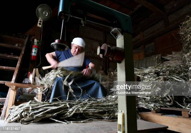 A worker makes bundles of mulberry wood at a mill that produces handmade paper at Iwano Heizaburo Seishi Sho Company in Echizen paper village on July...