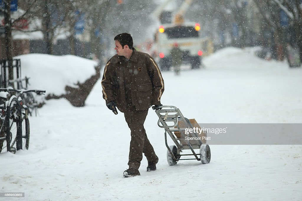 A UPS worker makes deliveries during a snow storm on February 5, 2014 in Burlington, Vermont. Burlington, and much of the Northeast, received another mix of wintery weather on Wednesday causing traffic accidents and hundreds of flight cancelations.