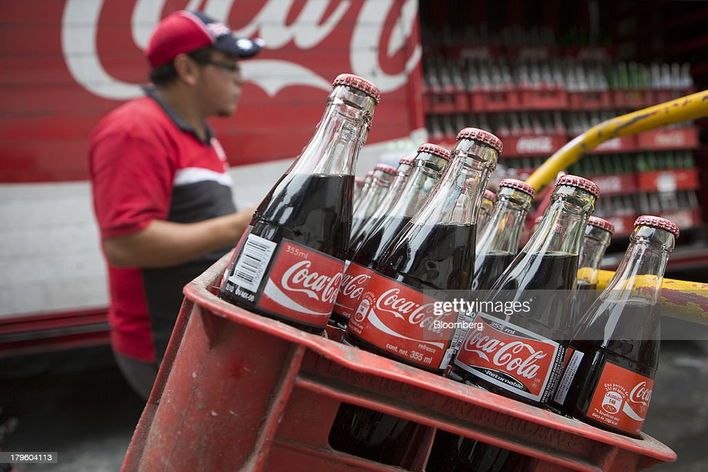 A worker makes deliveries of Coca-Cola products in Mexico City, Mexico, on Thursday, Sept. 5, 2013. Coca-Cola Femsa SAB, a bottler and distributor of Coca-Cola products in Mexico, agreed to buy Brazils Spaipa SA Industria Brasileira de Bebidas in a cash deal with a total transaction value of $1.86 billion. Photographer: Susana Gonzalez/Bloomberg via Getty Images