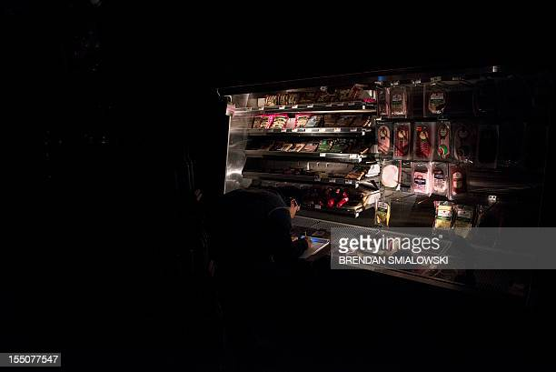 A worker makes notes at a refrigerator at Garden of Eden Gourmet which opened without power October 31 2012 in Hoboken New Jersey Hurricane Sandy...
