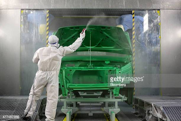 A worker manually sprays green paint to the body shell of a GAZon Next truck in the paint shop at the Gaz auto plant operated by Gaz Group in Nizhny...