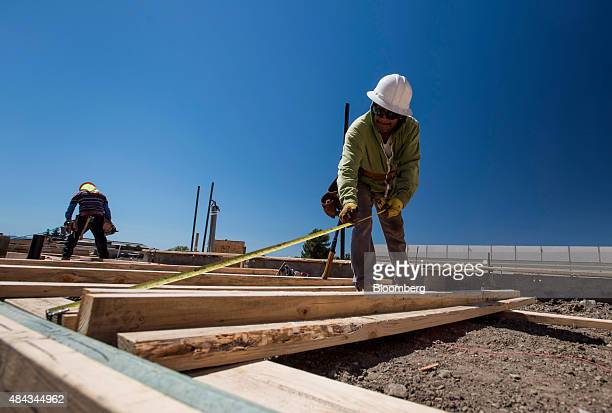 A worker measures a 2x4 piece of wood to be used for the wall of a house under construction at the KB Home Vineyard Crossing Community in Livermore...